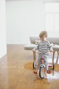 室内で三輪車をこぐ外国人男の子の写真素材 [FYI03235900]