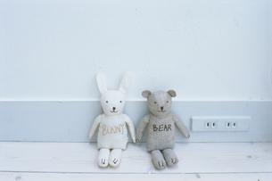壁に寄りかかるウサギとクマの人形の写真素材 [FYI03235991]