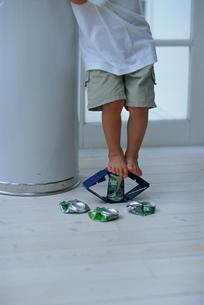 素足で空き缶をつぶす子供の写真素材 [FYI03235992]