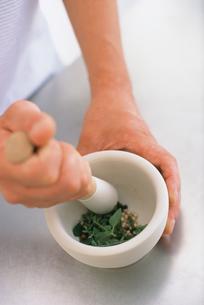 すり鉢でハーブをする男性の手元の写真素材 [FYI03236015]