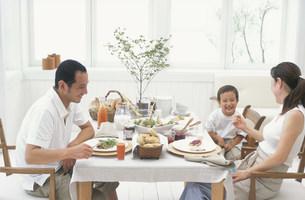食卓を囲む親子三人の写真素材 [FYI03236019]