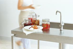 フルーツの瓶詰めのあるシンクと女性の写真素材 [FYI03236021]
