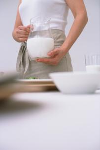 ミルクの入ったピッチャーを持つ女性の写真素材 [FYI03236023]