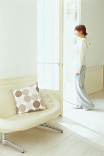 白いソファの脇の窓辺に佇む女性の写真素材 [FYI03236050]