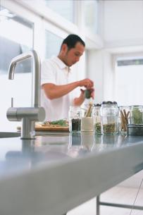 調理台の調味料と料理する男性の写真素材 [FYI03236054]