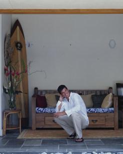 ソファの前にしゃがむ笑顔の男性の写真素材 [FYI03236095]