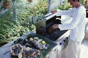バーベキューでロブスターを焼く男性の写真素材 [FYI03236133]