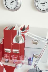 掛け時計の並んだ壁と赤系ステーショナリーのデスクの写真素材 [FYI03236262]