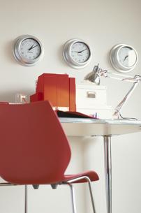 掛け時計の並んだ壁と赤系ステーショナリーのデスクの写真素材 [FYI03236263]