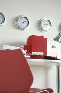 掛け時計の並んだ壁と赤系ステーショナリーのデスクの写真素材 [FYI03236264]