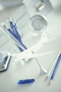 紙で出来た白い飛行機と青系ステーショナリーの写真素材 [FYI03236277]