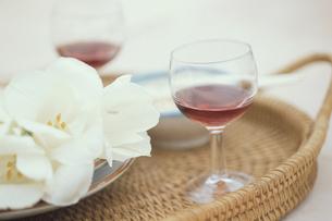 籐のお盆にワイン入りグラス2個・白チューリップの写真素材 [FYI03236776]