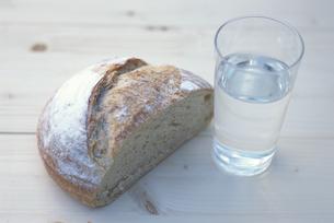 半分にスライスした丸パンとお水の入ったグラスの写真素材 [FYI03236778]