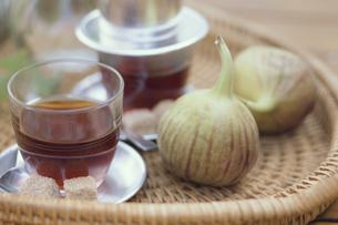 籐の平籠の上のベトナムグラスにコーヒーといちじく2個の写真素材 [FYI03236794]