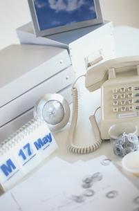 デスクの上の電話と時計の写真素材 [FYI03236974]