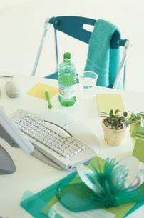 机の上のパソコンとグリーンのステーショナリーの写真素材 [FYI03237252]