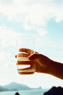 水の入ったグラスを持つ子供の手の写真素材 [FYI03238298]