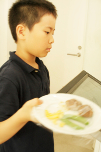 ご飯を電子レンジにかける男の子の写真素材 [FYI03238404]