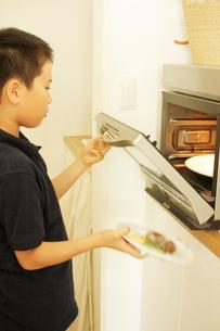ご飯を電子レンジにかける男の子の写真素材 [FYI03238405]
