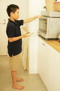 ご飯を電子レンジにかける男の子の写真素材 [FYI03238406]