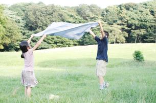 芝生でクロスを広げる女の子と男の子の写真素材 [FYI03238417]