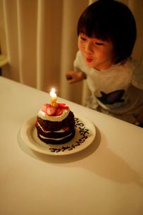 バースデーケーキのロウソクを吹き消す男の子の写真素材 [FYI03238453]
