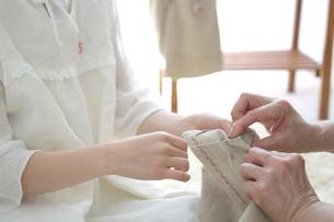 裁縫を習っている孫と祖母の手元の写真素材 [FYI03238513]