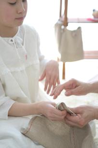裁縫を習っている孫と祖母の手元の写真素材 [FYI03238516]