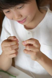 針に糸を通す女の子の写真素材 [FYI03238576]