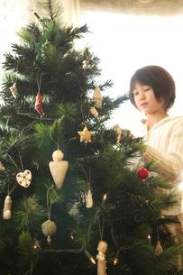 ツリーに飾り付けをする女の子の写真素材 [FYI03238633]