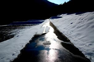 山間の逆光に光る雪解けの道路と残雪の田園の写真素材 [FYI03240733]