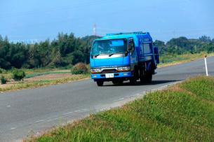 揖斐川の堤防を走り清掃工場に向かうごみの収集車の写真素材 [FYI03240934]
