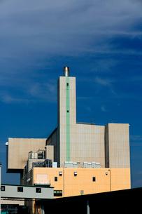 青空の下、煙突がそびえる白い清掃工場の建物の写真素材 [FYI03240935]