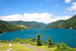青空、白い雲の下青い湖面の水をたたえる徳山湖の春の写真素材 [FYI03241007]