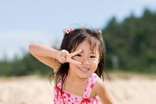 海で遊ぶピースサインの少女の写真素材 [FYI03241261]