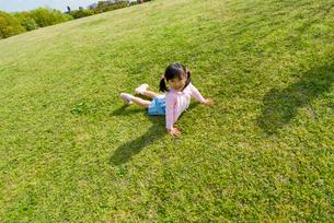 芝生の上に寝転ぶ女の子の写真素材 [FYI03241356]