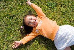 芝生の上に寝転ぶ女の子の写真素材 [FYI03241373]