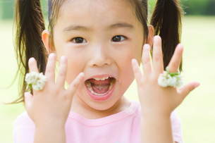 シロツメクサの指輪を付けた女の子の写真素材 [FYI03241376]