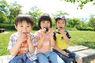 公園でおにぎりを食べる女の子と男の子3人の写真素材 [FYI03241470]