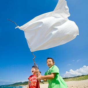 砂浜で白旗を持つ女の子と男の子の写真素材 [FYI03241503]