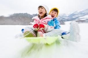 雪山でそりで遊ぶ女の子と男の子の写真素材 [FYI03241514]