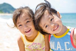 砂浜で微笑む男の子と女の子の写真素材 [FYI03241516]