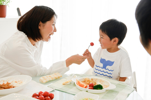 母親にトマトをもらう男の子の写真素材 [FYI03241712]