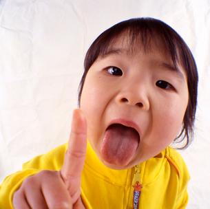 舌を出す女の子の顔のアップの写真素材 [FYI03241841]
