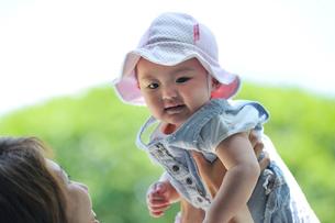 赤ちゃんを持ち上げる母親の写真素材 [FYI03243850]