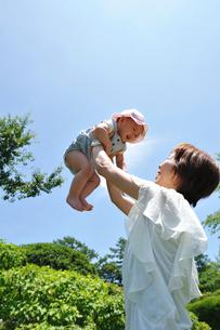 赤ちゃんを高く持ち上げる母親の写真素材 [FYI03243872]