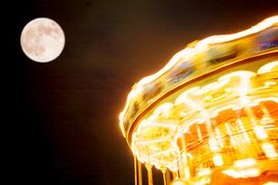 夜のメリーゴーラウンドと満月の写真素材 [FYI03244532]