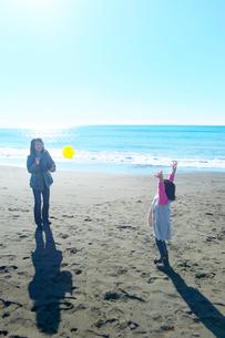 海岸でボール遊びをする親子の写真素材 [FYI03244697]