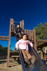 すべり台で遊ぶ男の子と女の子の写真素材 [FYI03244708]