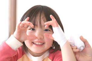 包帯を巻いてもらう女の子の写真素材 [FYI03244716]
